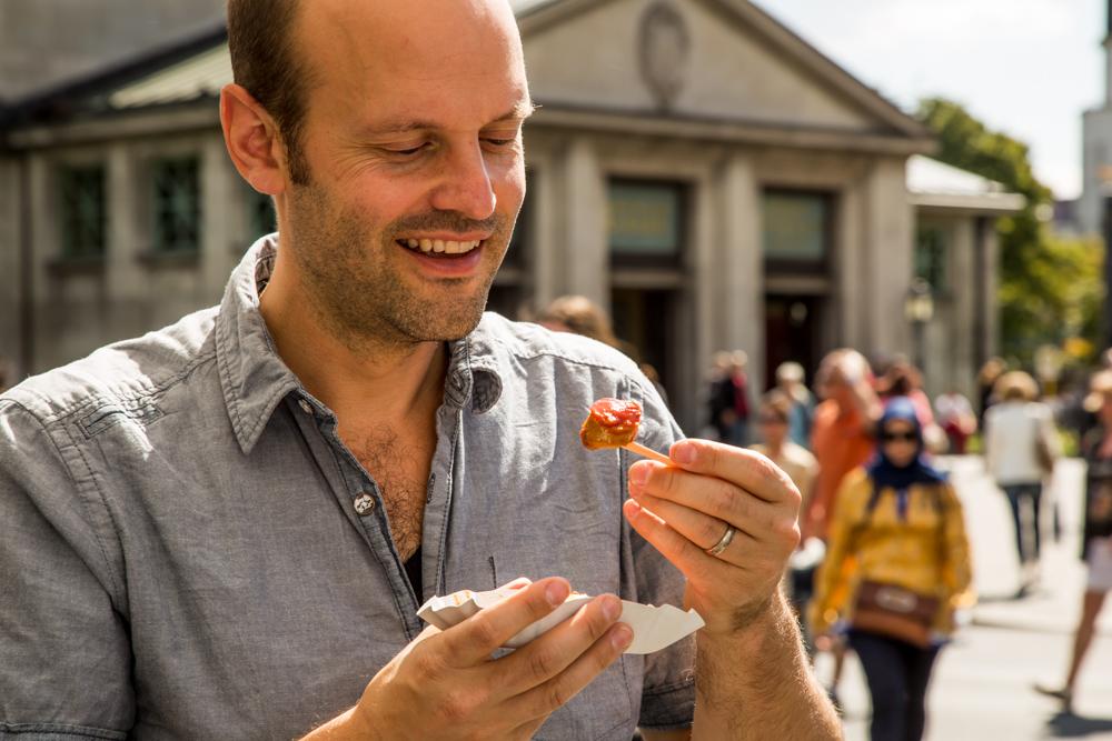 Try Foods Gründer Jörn Gutowski probiert Currywurst am Wittenbergplatz (Foto: Ole Schwarz)